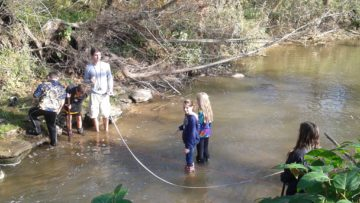 High school students work with elementary students to gather data from the creek.
