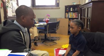 One of the Men of Mitchell helps a younger student during a mentoring session.