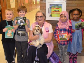 Elementary students read to furry friends