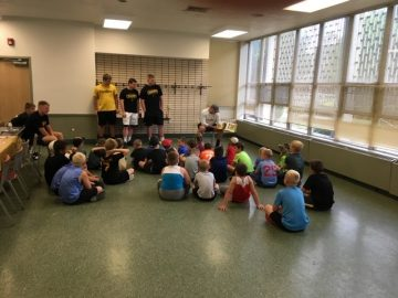 High school football players read to students in Community Recreation Program